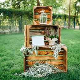 Rustic wedding outdoor photo zone. Hand made wedding decorations includes wooden boxes, flowers and plate Love Is In The Air.